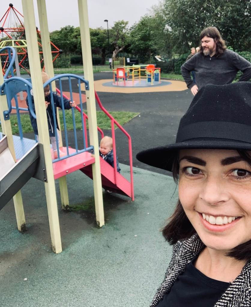 Two young children wearing raincoats play on a colourful playground slide. Woman, front right, taking the selfie, smiling, wears a black fedora. Behind her a man with long hair and beard has hands on waist while looking over the children. It is a rainy day.